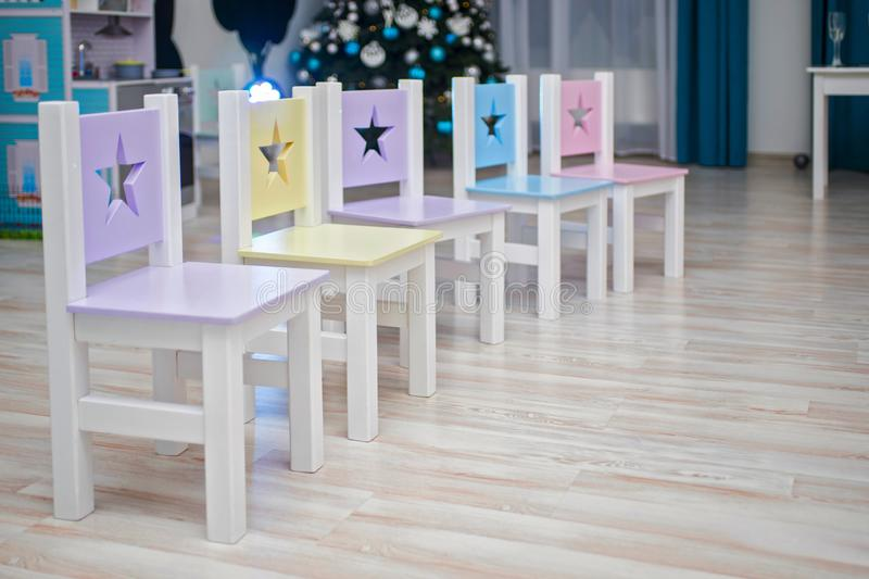 Chairs in children`s room. Kids room Interior. Chairs in kindergarten preschool classroom. Many brightly colored chairs for royalty free stock photos