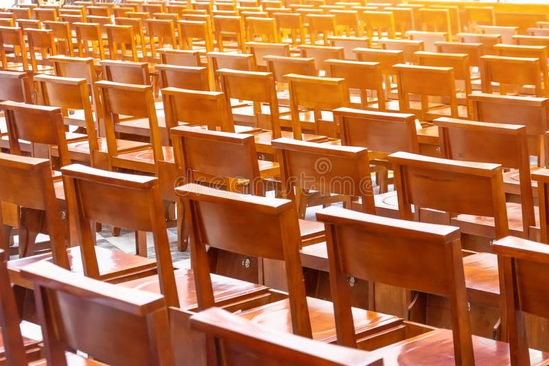 Chairs in the church in the prayer hall, wooden brown armchairs in rows behind royalty free stock images
