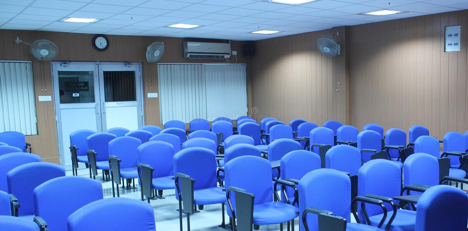 Chairs in a class room. Chairs and desks in a class room in a row royalty free stock images
