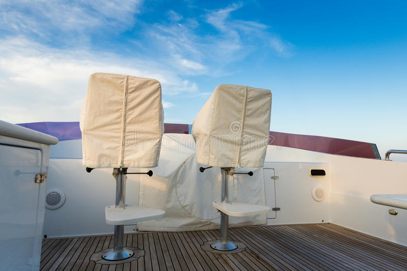 Chairs and the control panel the yacht in covers. The parking covered for a season stock photography