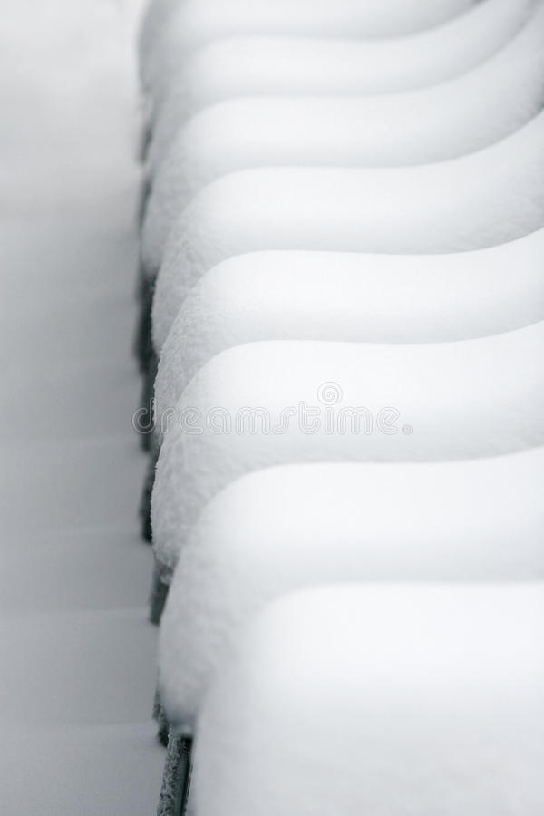 Chairs covered in snow. An abstract background of lines made of chairs covered in snow royalty free stock photography
