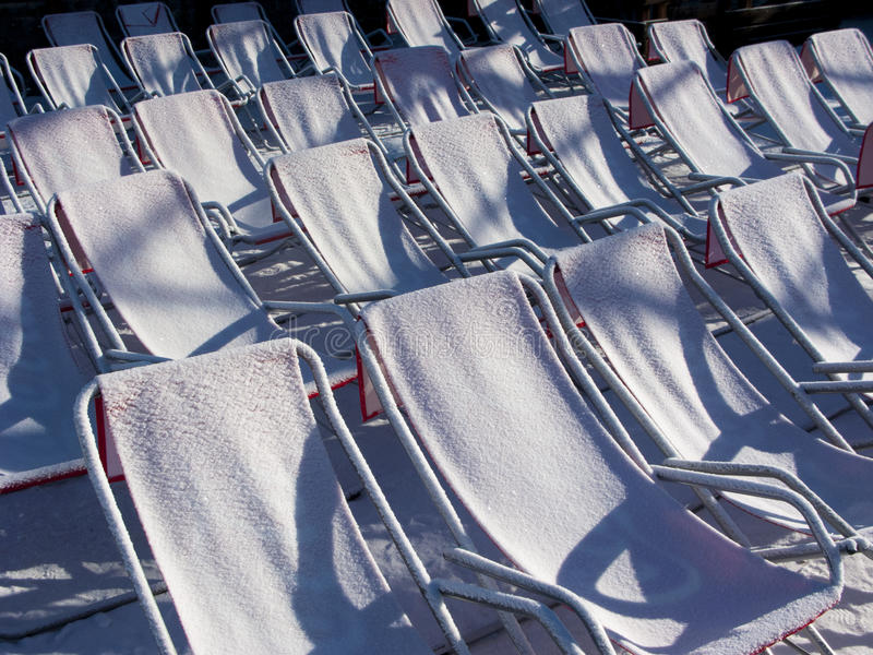 Chairs covered with snow. Reclining chairs covered in snow in early morning light stock photos