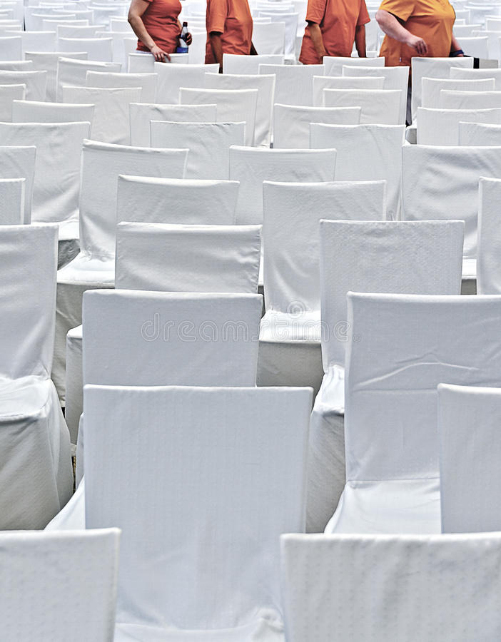 Chairs with covers. Rows of chairs with covers made of white fabric and women with orange clothes royalty free stock images