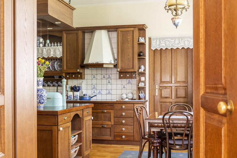 Chairs at dining table in classic wooden kitchen interior with i. Sland. Real photo royalty free stock photos
