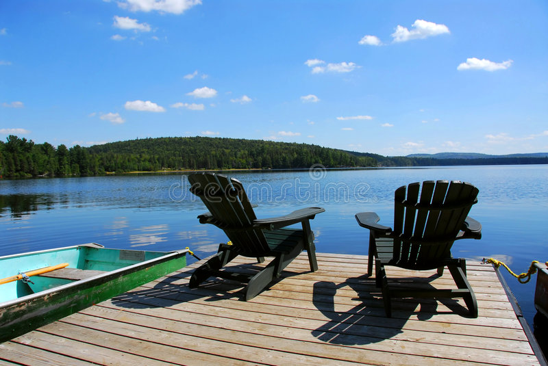 Chairs on dock. Two adirondack wooden chairs on dock facing a blue lake with clouds reflections