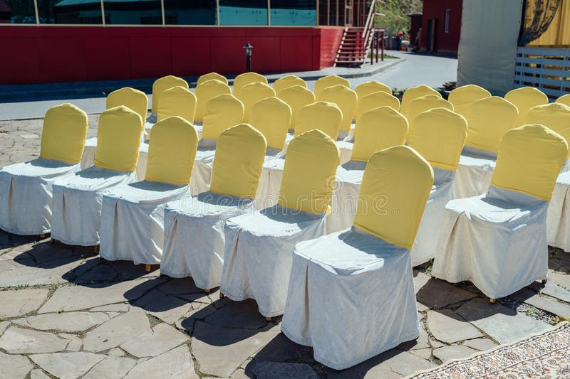 Chairs for guests on wedding ceremony with white and yellow satin cloth outdoor. Chairs for guests on wedding ceremony with white and yellow satin cloth outdoor royalty free stock photos