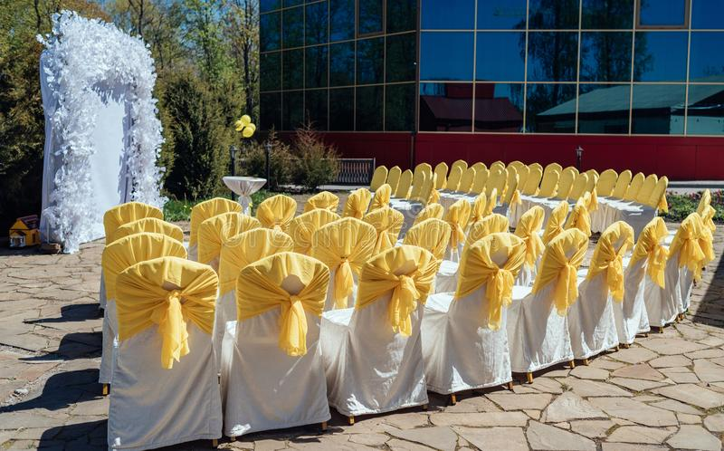 Chairs for guests on wedding ceremony with white and yellow satin cloth outdoor. Chairs for guests on wedding ceremony with white and yellow satin cloth outdoor stock image