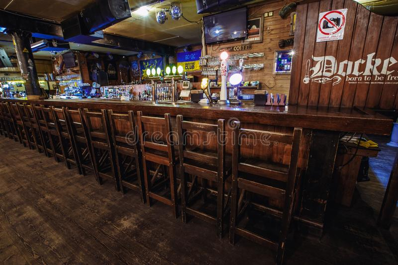 Chairs lined up along the bar. Kiev, Ukraine- March 19, 2018. wooden tall chairs lined up along a bar counter in an Irish pub pub. behind the chairs is a dance stock photos