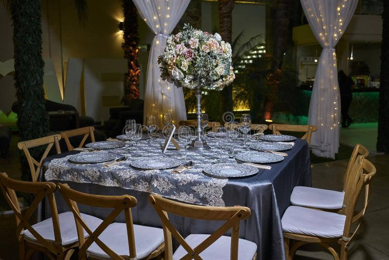 Romantic party table setting, elegant ballroom for wedding reception, decoration ideas, flowers centerpiece. 10 chairs luxurious romantic party table setting lit royalty free stock images