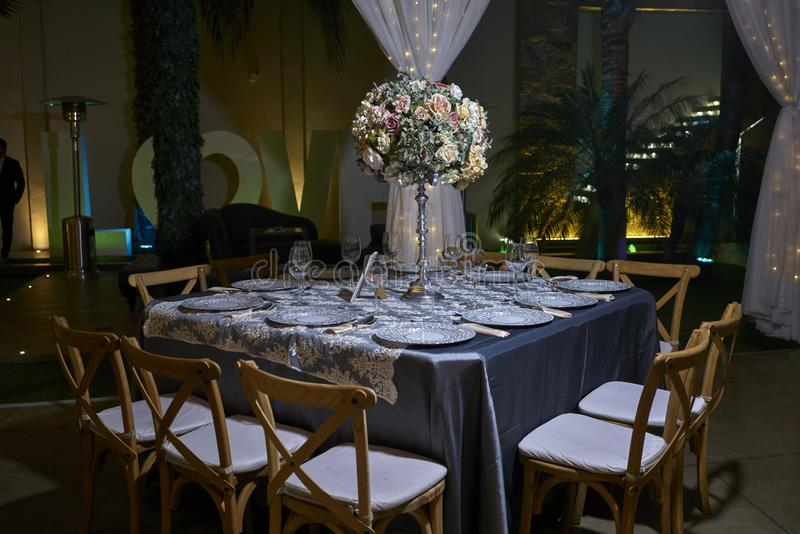 10 chairs table setting, elegant ballroom for wedding reception, decoration ideas, flowers centerpiece. 10 chairs luxurious romantic party table setting lit by royalty free stock photo