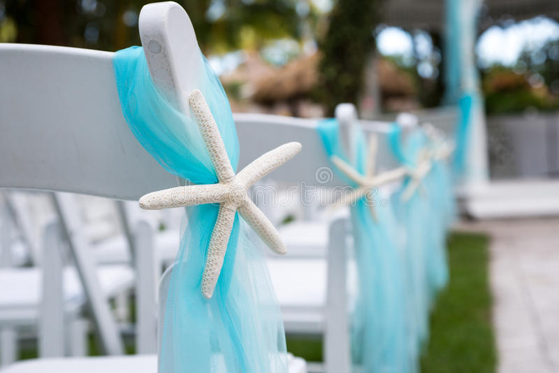 Chairs at outdoor wedding. White chairs decorated with turquoise material at outdoor wedding with altar in background royalty free stock photography