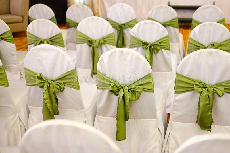 chairs for a party with green covers ribbon and bow stock image