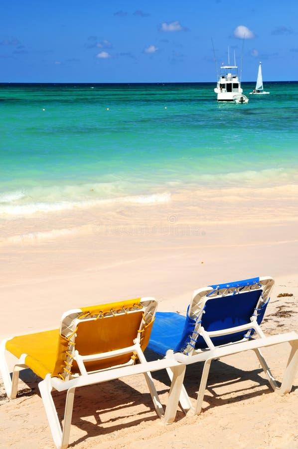 Chairs on sandy tropical beach royalty free stock photos