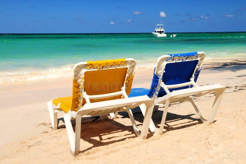 Chairs on sandy tropical beach stock photos