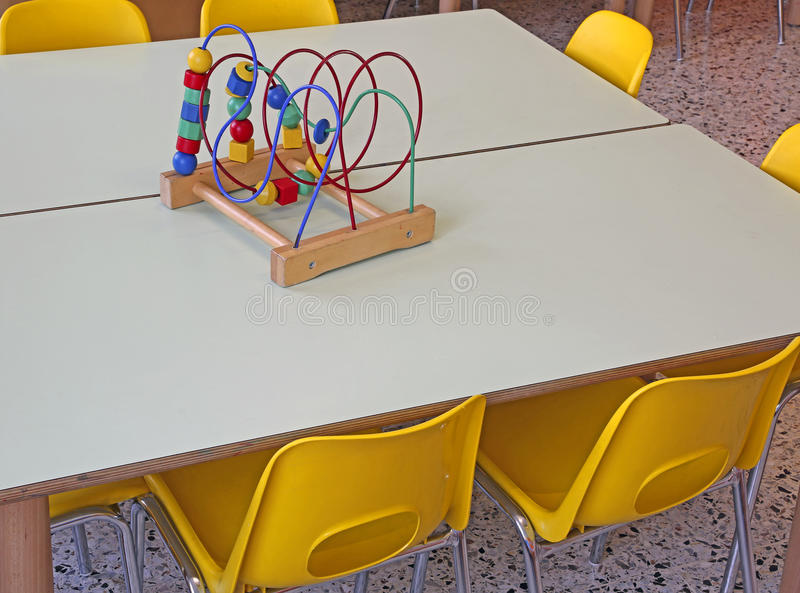 Chairs with small benches inside a daycare. Yellow chairs with small benches inside a daycare stock photos