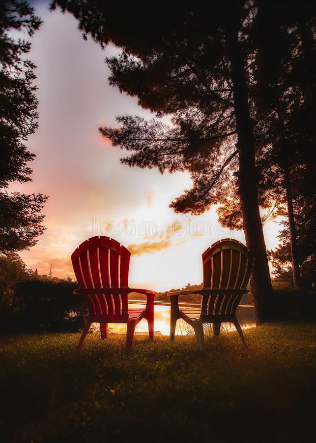 Chairs on Table Against Trees during Sunset stock images