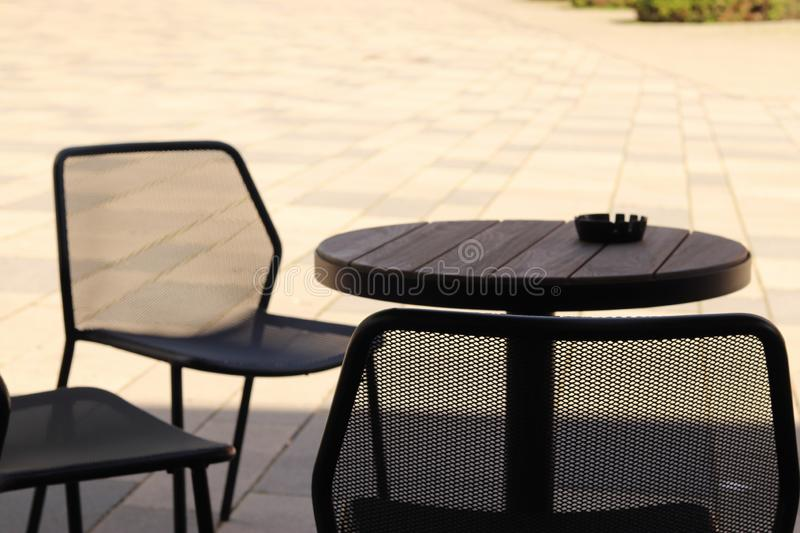 Chairs, table with an ashtray in the shadow with a sunny background. Rest, set, modern, tranquil, coffee, outdoors, closeup, spring, design, wood, day, white royalty free stock images