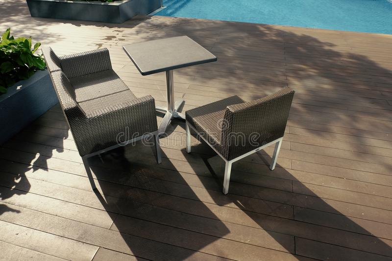 chairs and table side near the pool ideal for travel and vacation concept.bright sunny day and shadow on wooden platform royalty free stock photos