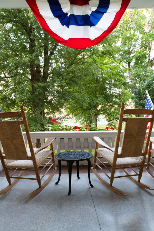 Chairs and Table at the Terrace with American Flag. Two Wooden Rocking Chairs with Small Table at the Terrace with Conceptual American Flag Fronting Tall Green royalty free stock images
