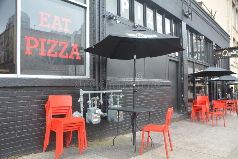 Chairs, tables, and umbrellas against a black wall in Portland, OR. Here are red chairs with black tables and umbrellas against a black wall in downtown Portland royalty free stock photo