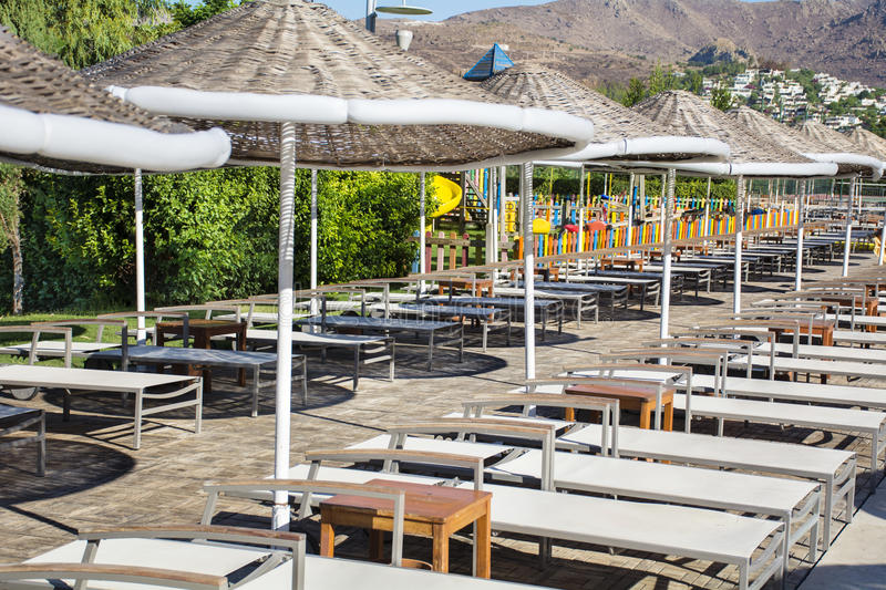 Chairs and thatched umbrellas around a swimming pool stock images