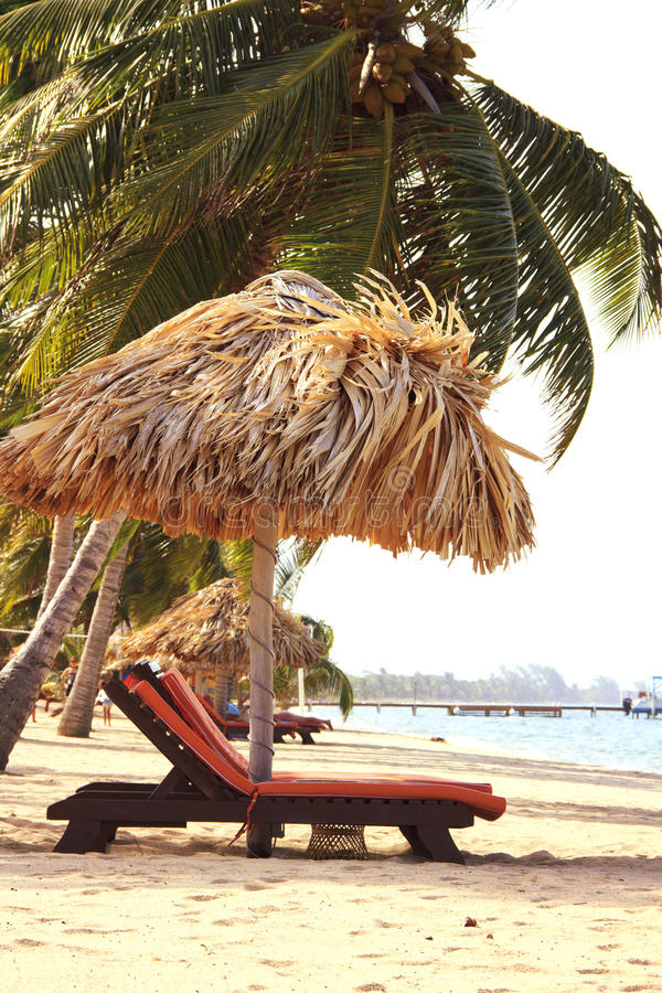 Chairs and a tiki hut on the beach stock images