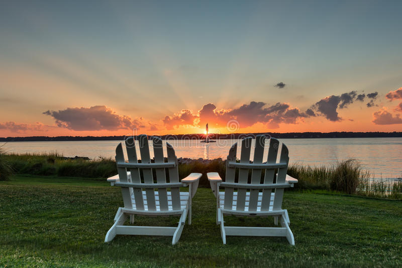 Chairs for Two. Two chairs facing Hilton Head bay viewing an iconic sunset with rays of light extending beyond the clouds stock image