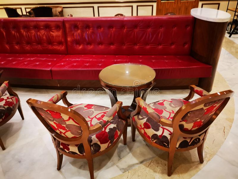 Chairs and vintage table near red sofa. Of leather - hotel lobby royalty free stock photography