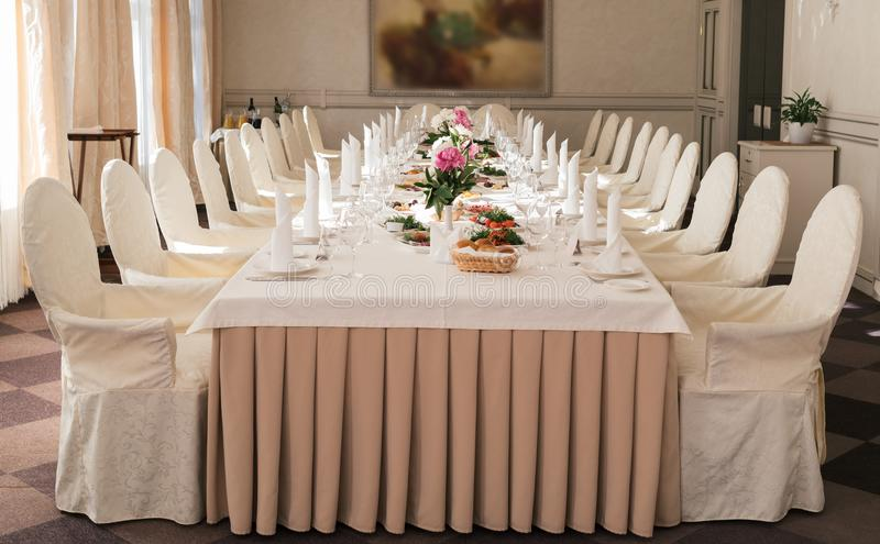 Chairs with white cloth and table for guests served for wedding. royalty free stock images