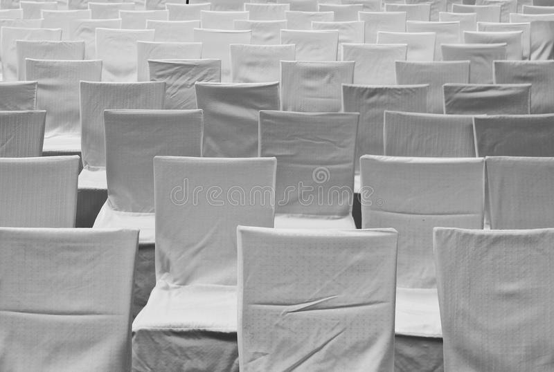 Chairs with white covers. Rows of chairs with covers made of white fabric royalty free stock photography