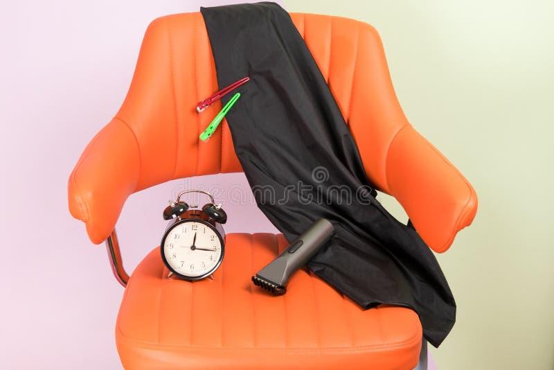 Chaise avec des accessoires pour un maître de cheveu-coupe, heure d'aller à un salon de beauté images libres de droits