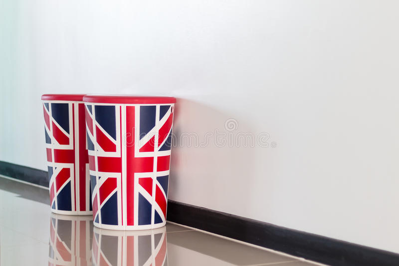 Chaise avec le drapeau britannique sur le fond d'un mur blanc photos libres de droits