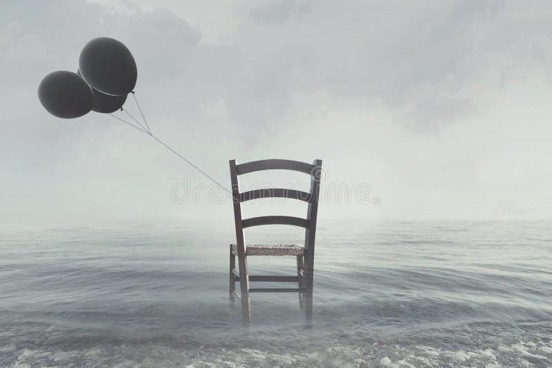 chaise avec les ballons noirs attachés au rivage d'océan photographie stock