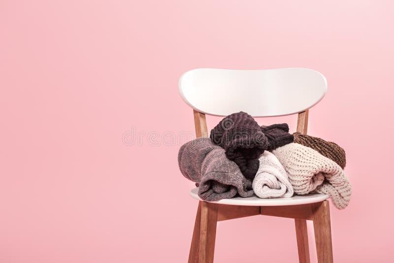 Chaise blanche avec une pile de chandails tricotés sur un fond rose photos stock