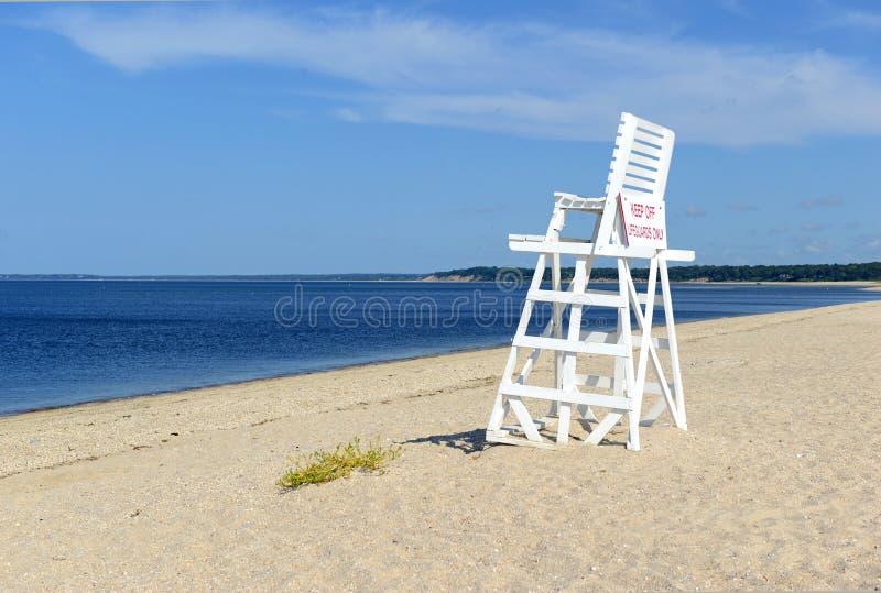 Chaise blanche de maître nageur sur la plage vide de sable avec le ciel bleu photographie stock libre de droits