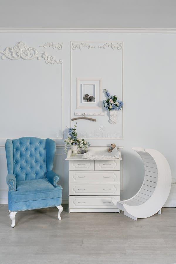 Chaise bleue et table changeante pour des nourrissons intérieur d'une salle spacieuse du ` s d'enfants photos stock