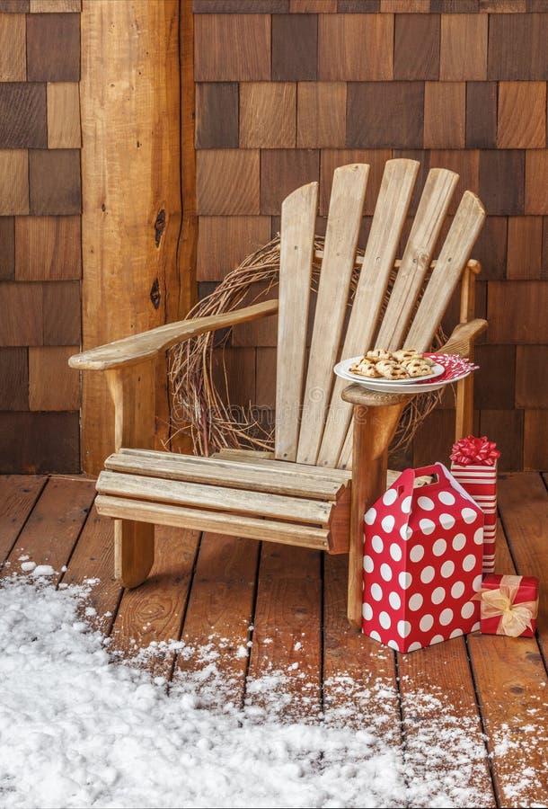 Chaise d'Adirondack avec des cadeaux de Noël sur la plate-forme en bois neigeuse de porche d'une carlingue rustique de pays Maiso image libre de droits