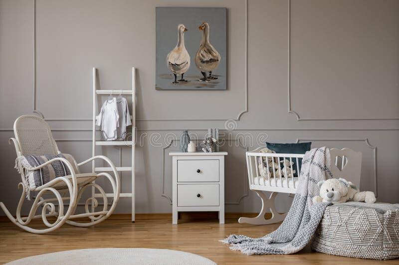 Chaise de basculage en bois blanche avec l'oreiller à côté de l'échelle scandinave, le coffre des tiroirs et le berceau, l'espace photos libres de droits