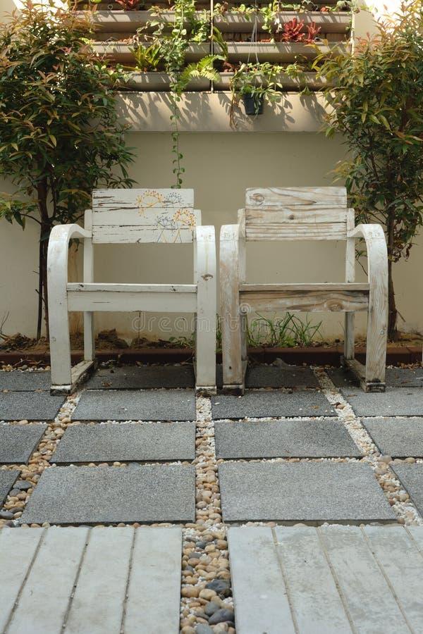 Chaise de deux bras dans peu de jardin images stock