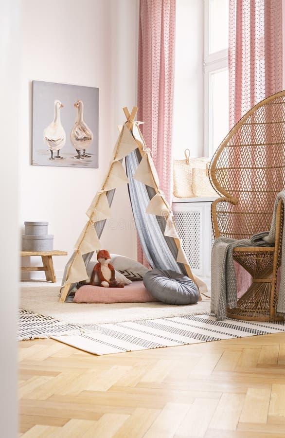 Chaise de paon à côté de tente avec le jouet de renard dans l'intérieur de la chambre de l'enfant avec l'affiche et la couverture images libres de droits