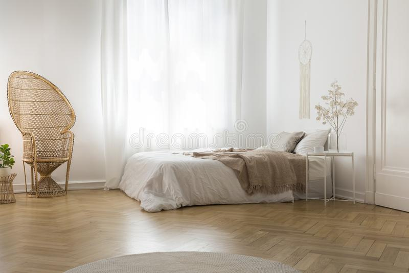 Chaise de paon de rotin à côté de fenêtre dans l'intérieur blanc de chambre à coucher avec la couverture sur le lit photos libres de droits