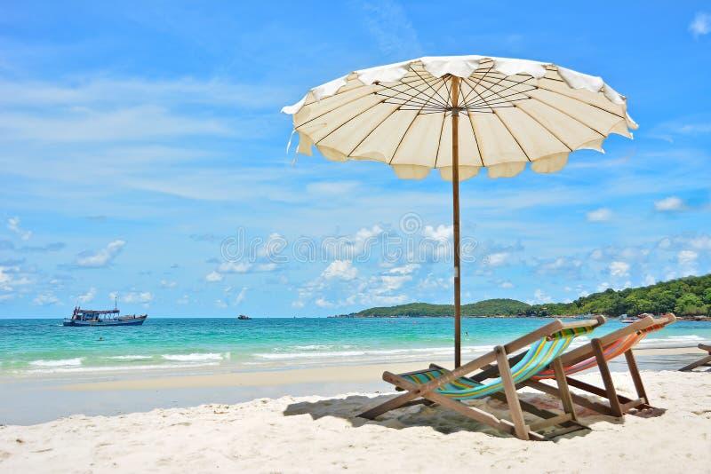 Chaise de plage avec le parapluie photos stock