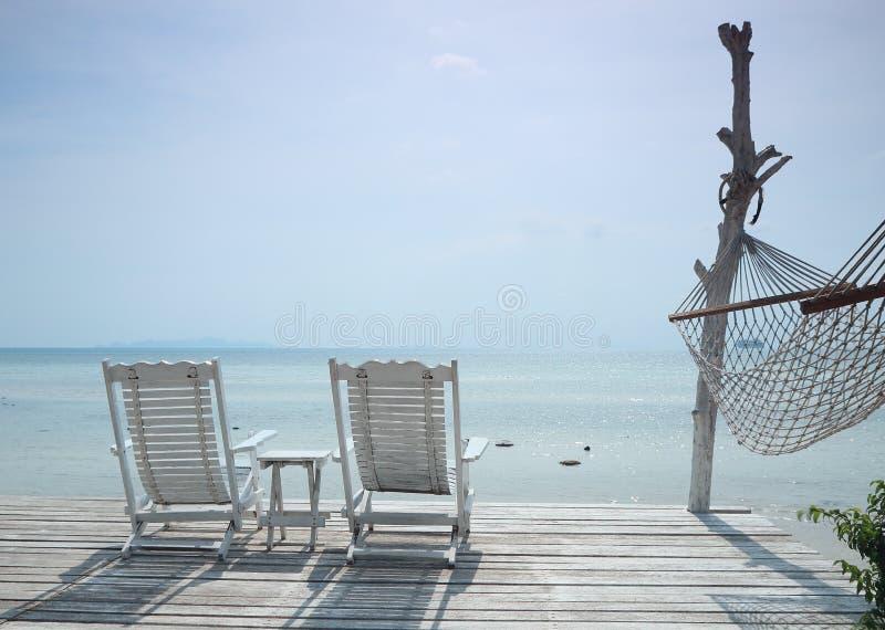 Chaise de plage confortable et hamac blancs faisant face au paysage marin photos libres de droits