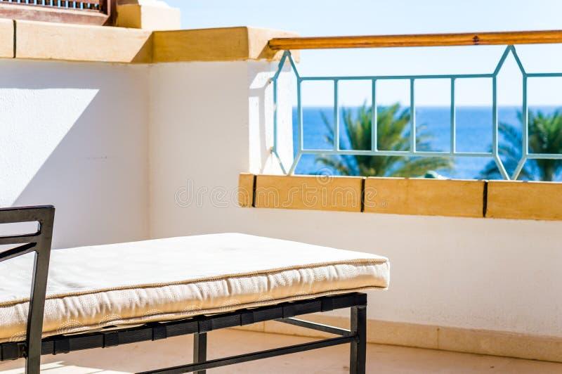Chaise de plate-forme sur le balcon de l'hôtel avec la vue de mer images libres de droits