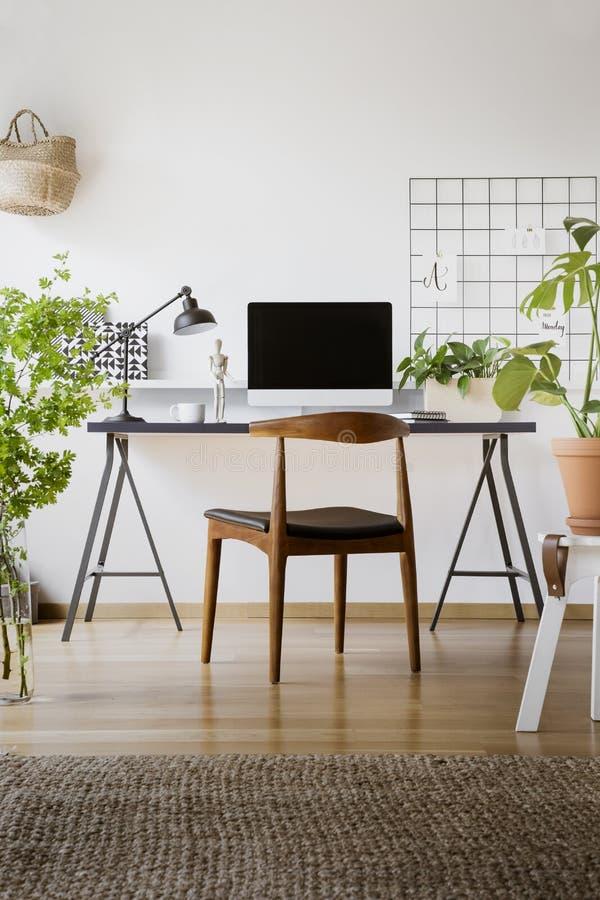 Chaise en bois au bureau avec la lampe et l'ordinateur de bureau dans l'offi à la maison photos libres de droits