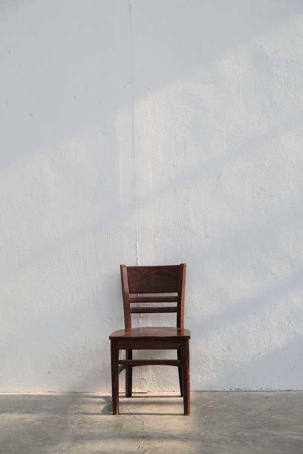 Chaise en bois brune simple avec le rayon léger de la fenêtre sur le fond blanc de mur photos libres de droits