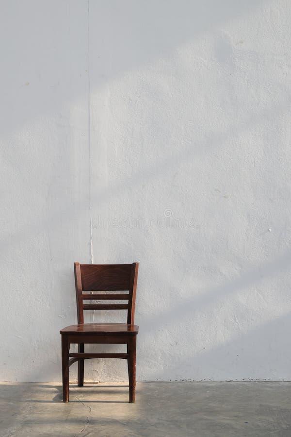 Chaise en bois brune simple avec le rayon léger de la fenêtre sur le fond blanc de mur photos stock