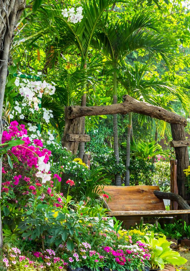 Chaise en bois dans le jardin de fleurs photographie stock libre de droits