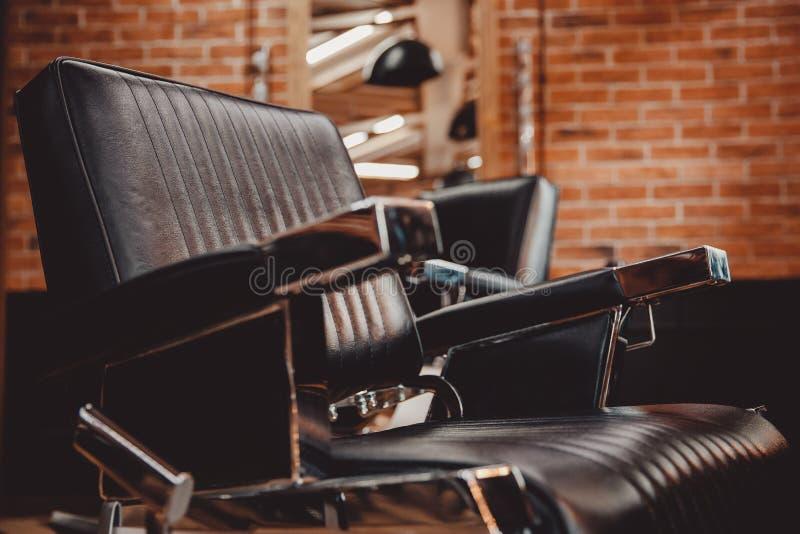 Chaise en cuir de raseur-coiffeur de cru, mur de briques Le salon de coiffure des hommes de hippie de concept photos stock