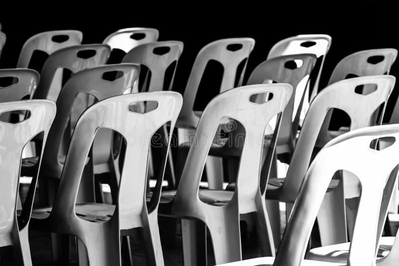 Chaise en plastique empilée au soleil et dans l'ombre photographie stock